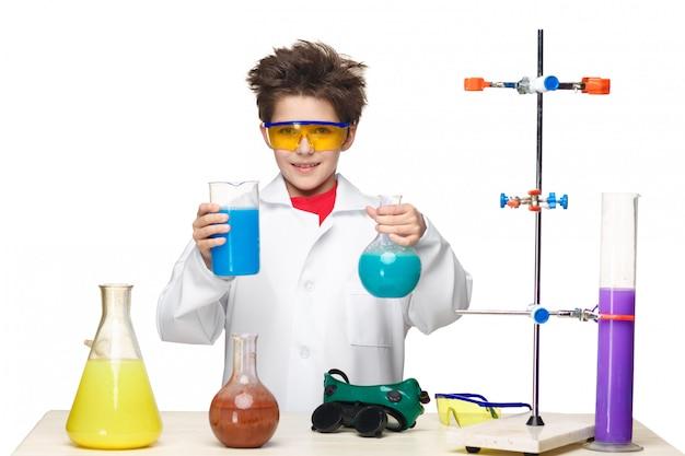 Kleiner junge als chemiker, der im labor mit chemischer flüssigkeit experimentiert
