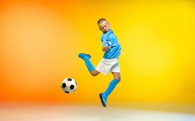 Kleiner junge als fußball- oder fußballspieler in sportbekleidung, der an einer wand mit farbverlauf übt