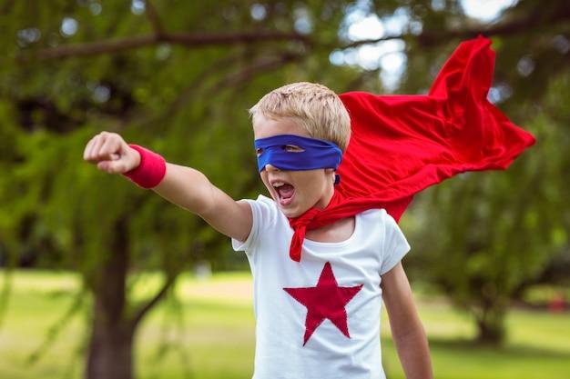 Kleiner junge als supermann verkleidet