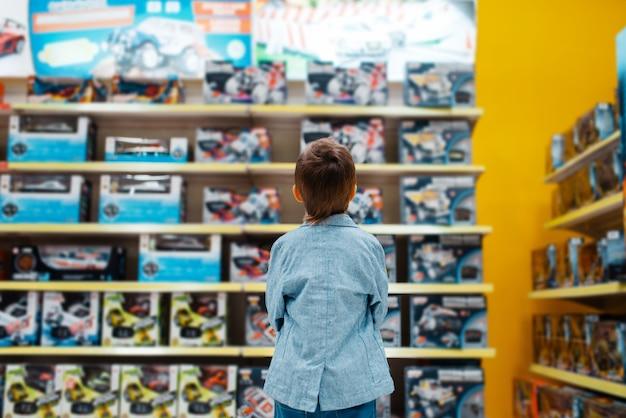 Kleiner junge am regal im kinderladen, rückansicht. sohn, der spielzeug im supermarkt wählt