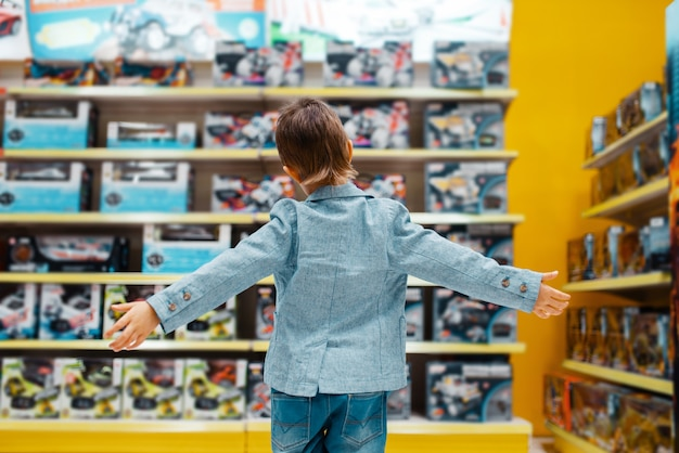 Kleiner junge am regal im kinderladen, rückansicht
