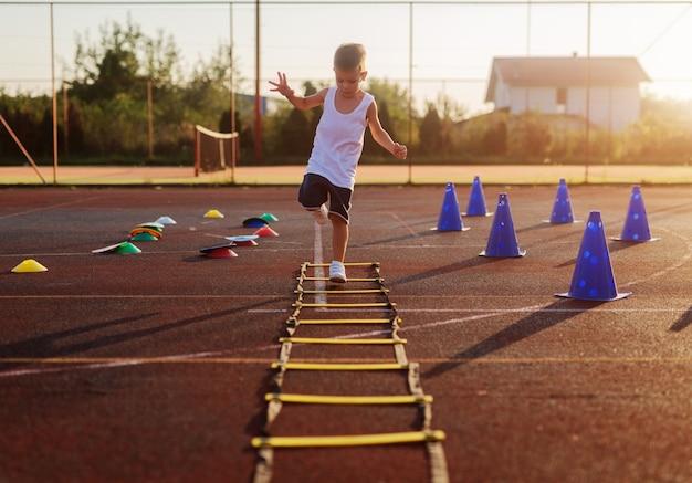 Kleiner junge am sommertraining des frühen morgens, der über trammels im trainingsfeld springt.