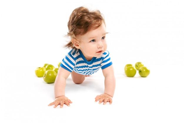 Kleiner junge auf dem boden mit grünen äpfeln