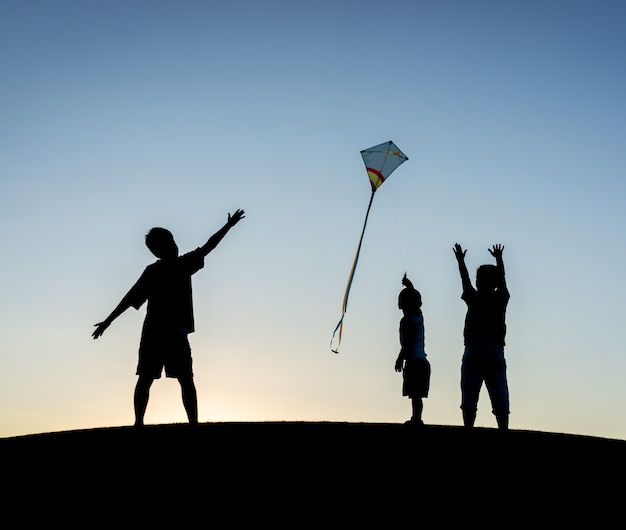 Kleiner junge auf den sommerferien, die spaß und glücklichen zeitfliegendrachen auf dem seestrand haben