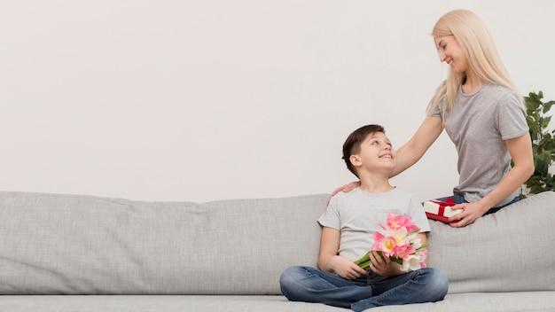 Kleiner junge auf der couch mit geschenken für mama