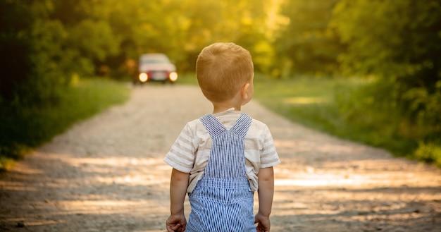 Kleiner junge auf einer straße im wald Premium Fotos