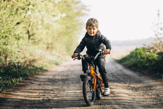 Kleiner junge auf fahrrad im park