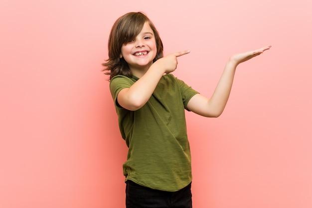 Kleiner junge aufgeregt, einen kopienraum auf palme halten.