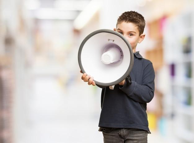 Kleiner junge aufträge mit einem megaphon geben