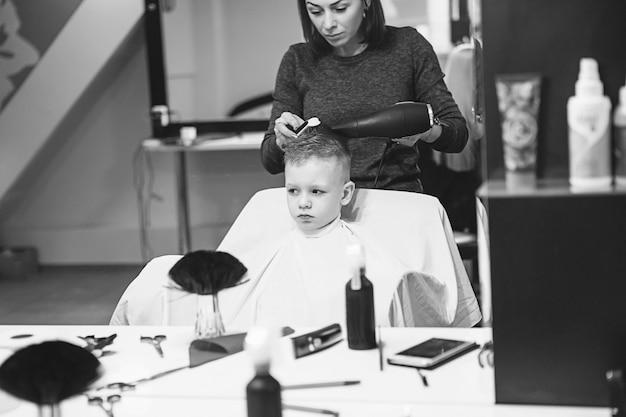 Kleiner junge beim friseur. kind hat angst vor haarschnitten. die hände des friseurs machen dem kleinen jungen die frisur, ganz nah. modischer haarschnitt für jungen.