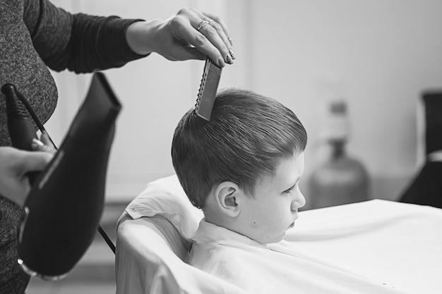 Kleiner junge beim friseur. kind hat angst vor haarschnitten. die hände des friseurs machen dem kleinen jungen die frisur, ganz nah