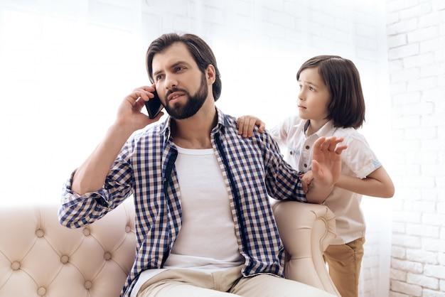 Kleiner junge benötigt aufmerksamkeit vom beschäftigten vater.