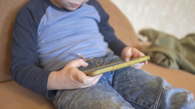Kleiner junge benutzt telefon, um zu spielen oder zu lernen, zu hause zu bleiben