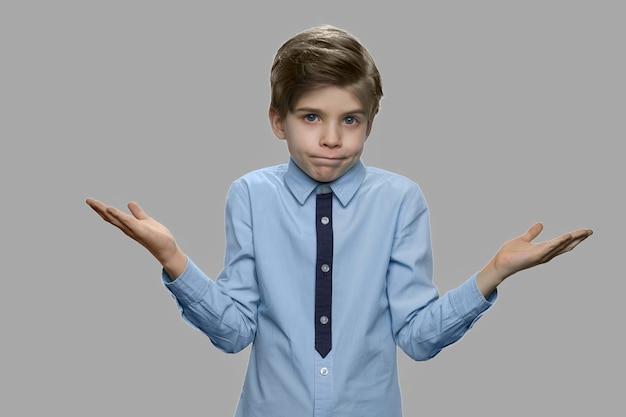 Kleiner junge breitete die hände zur seite aus. stilvolles europäisches kind mit achselzuckengeste. menschliche körpersprache.