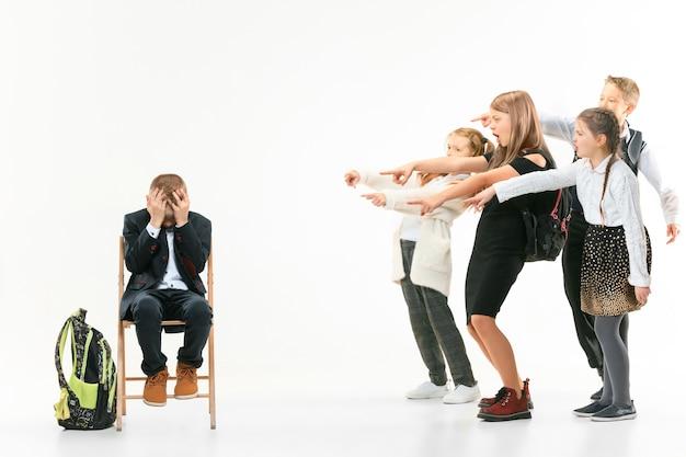 Kleiner junge, der allein auf stuhl sitzt und mobbing erleidet, während kinder verspotten