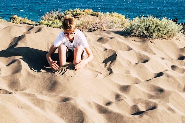 Kleiner junge, der allein mit sand am strand spielt