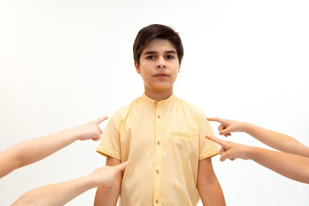 Kleiner junge, der allein steht und einen akt des mobbings erleidet, während kinder sich in der wand verspotten
