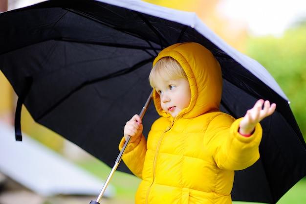Kleiner junge, der am regnerischen bewölkten herbstwetter geht. kind mit großem schwarzem regenschirm im regen. outdoor-aktivität fallen
