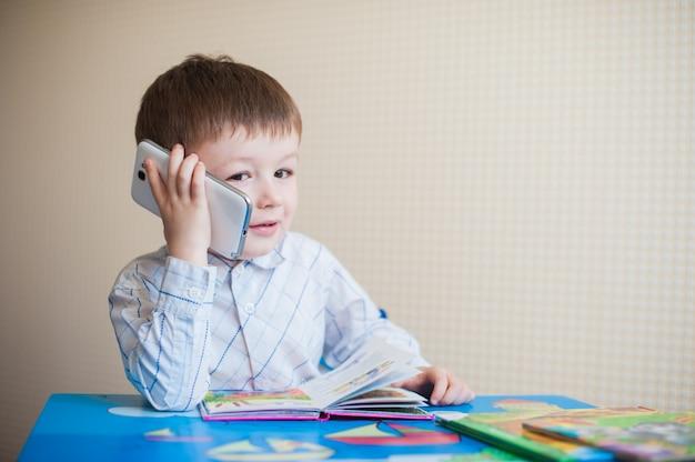 Kleiner junge, der am schreibtisch sitzt und am telefon spricht