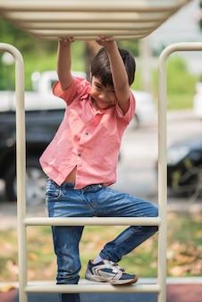 Kleiner junge, der am spielplatzklettern spielt