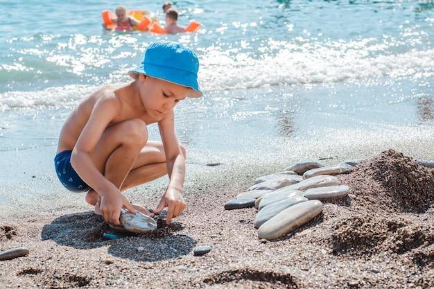Kleiner junge, der am strand am meer in sand und in den steinen spielt. sandburgen bauen.