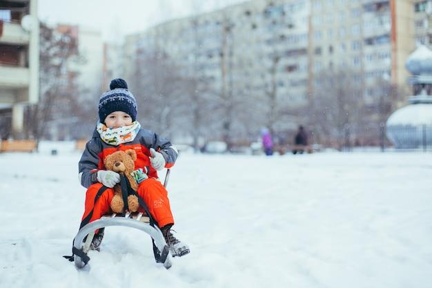 Kleiner junge, der am weihnachtstag in roten kleidern im schnee rodelt