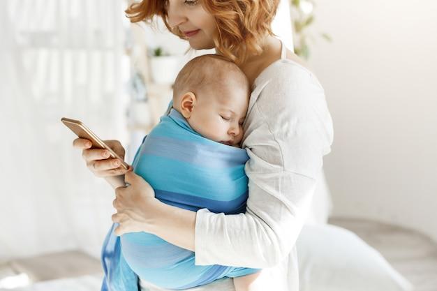 Kleiner junge, der angenehme träume in der babyschlinge hat, während mutter ruht und durch soziale netzwerke auf smartphone schaut. familien-, lifestyle-konzept.
