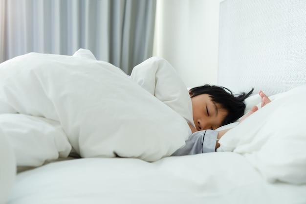 Kleiner junge, der auf bett am schlafzimmer schläft