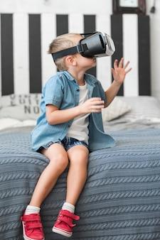 Kleiner junge, der auf bett unter verwendung der schutzbrillen der virtuellen realität sitzt