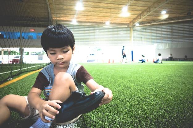 Kleiner junge, der auf dem fußballsportgebiet sitzt