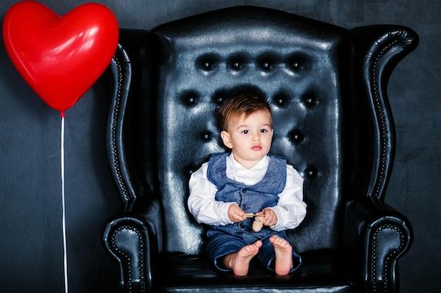 Kleiner junge, der auf dem lehnsessel mit rotem gestaltetem bild am st.-valentinstag sitzt.