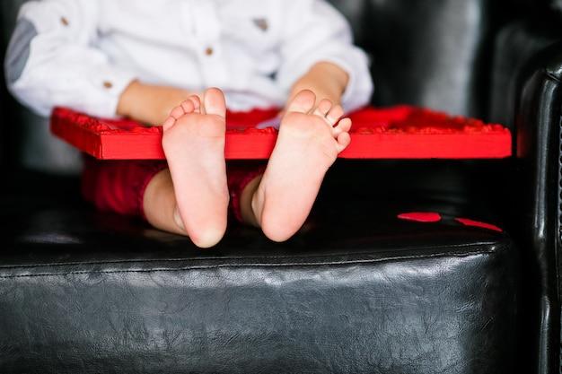 Kleiner junge, der auf dem lehnsessel mit rotem gestaltetem bild am valentinstag sitzt; kleine füße nahaufnahme