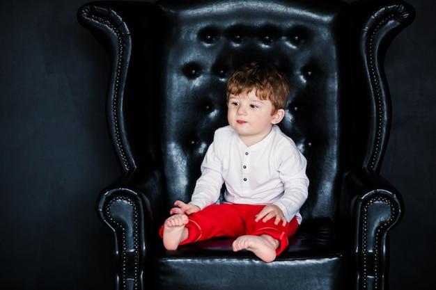 Kleiner junge, der auf dem lehnsessel mit rotem gestaltetem bild am valentinstag sitzt
