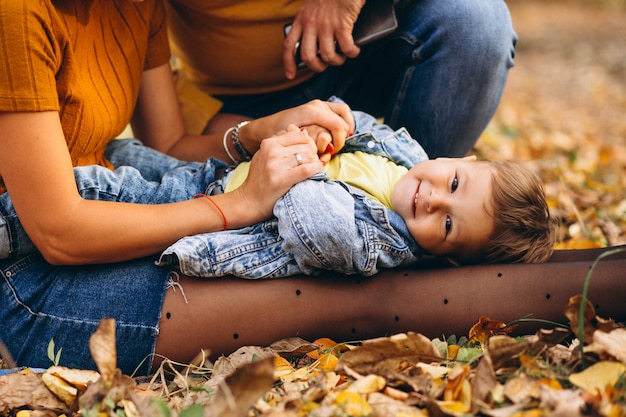 Kleiner junge, der auf den knien der mutter im park liegt