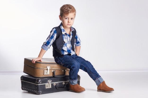 Kleiner junge, der auf den koffern, feiertag vorbereitend sitzt