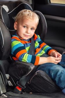 Kleiner junge, der auf einem autositz sitzt, schnallte sich im auto an.