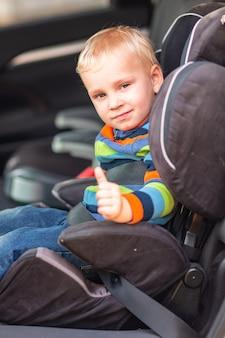 Kleiner junge, der auf einem autositz sitzt, schnallte sich mit dem daumen oben im auto an.