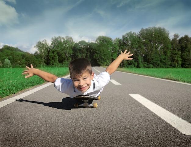 Kleiner junge, der auf einem skateboard spielt