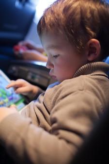 Kleiner junge, der auf einem tablet-computer spielt