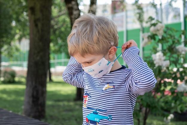 Kleiner junge, der auf einer parkbank sitzt und eine schutzmaske trägt