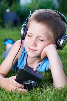 Kleiner junge, der auf gras mit altem audiokassettenrecorder liegt