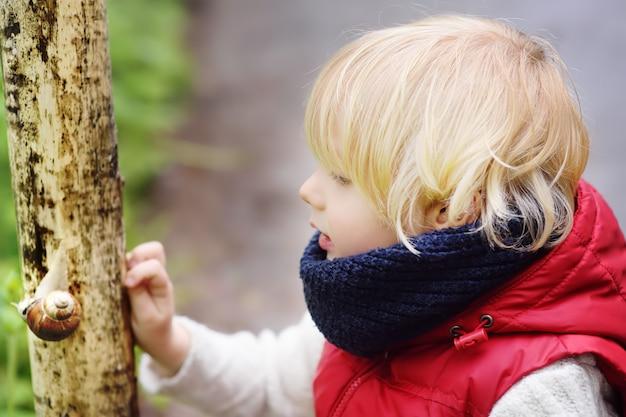 Kleiner junge, der auf großer schnecke während der wanderung im wald schaut
