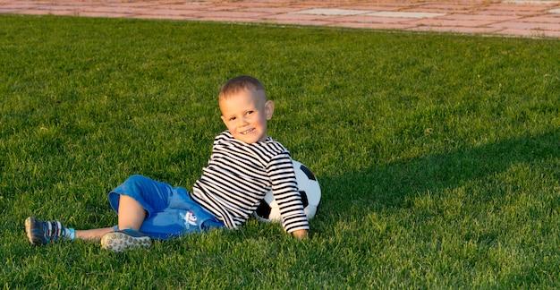 Kleiner junge, der auf grünem gras im abendsonnenlicht liegt, das sich gegen einen fußball zurücklehnt