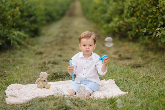 Kleiner junge, der auf picknickplaid im bauerngarten sitzt