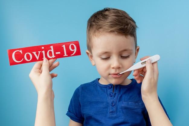 Kleiner junge, der auf rotes papier mit mesaage coronavirus auf blauem hintergrund zeigt
