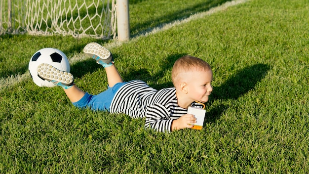 Kleiner junge, der auf seinem bauch im grünen gras gerade vor den torpfosten auf einem fußballfeld mit seinem fußball neben ihm liegt