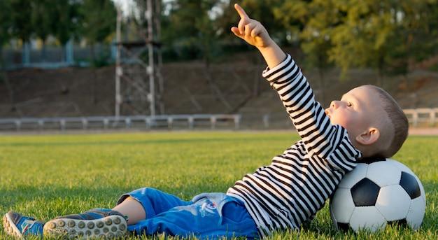 Kleiner junge, der auf seinem rücken im grünen gras liegt, wobei sein kopf auf einem fußball ruht, der zum himmel zeigt