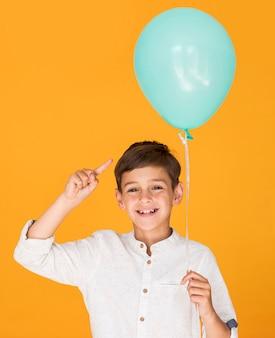 Kleiner junge, der auf seinen blauen ballon zeigt