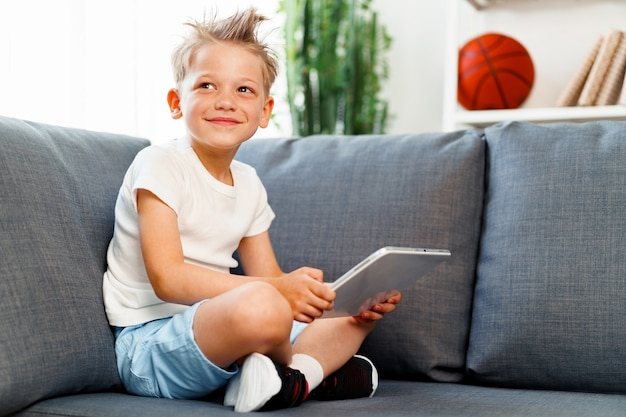 Kleiner junge, der auf sofa sitzt und digitales tablett zu hause verwendet