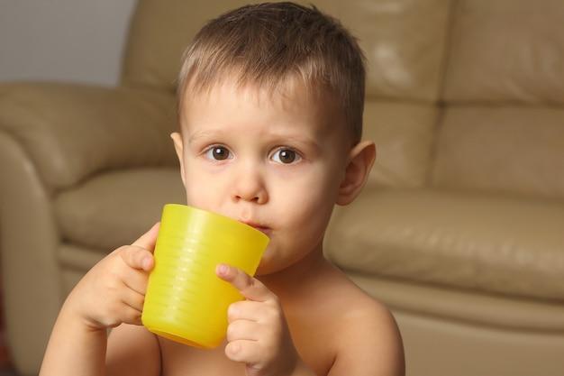Kleiner junge, der aus einem plastikbecher trinkt